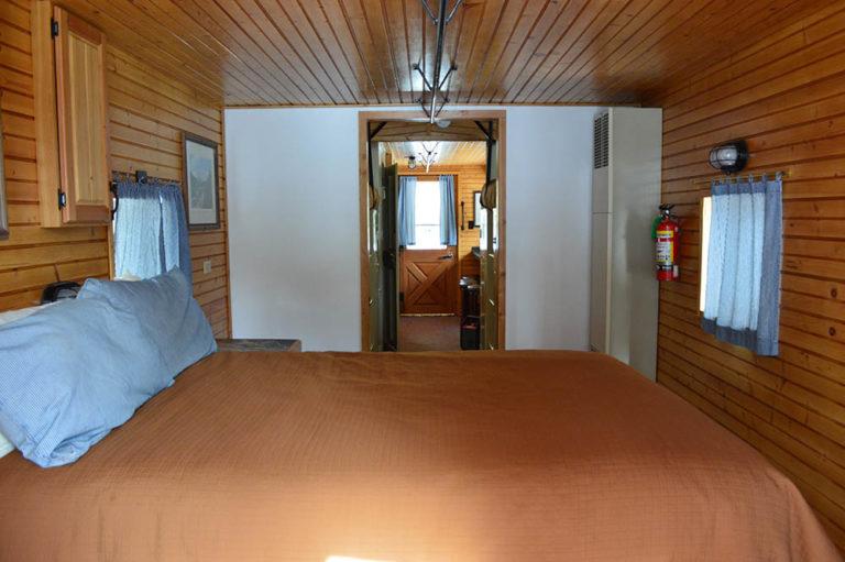 Queen bed in blue caboose at Izaak Walton Inn - Cabin Rentals in Glacier