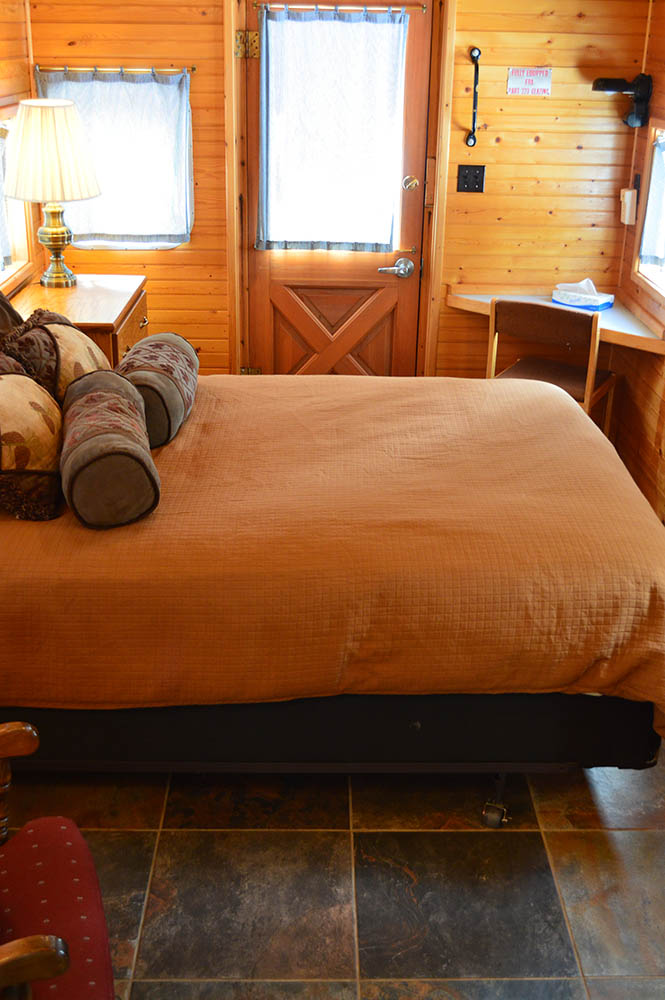 Queen bed in Green Caboose - Cabin Rentals in Glacier